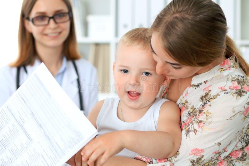 Niño del niño pequeño con su madre después del examen de la salud en la oficina del ` s del doctor imagen de archivo