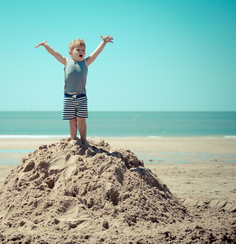 Niño del niño pequeño que se coloca en una colina en la playa con sus brazos fotos de archivo libres de regalías