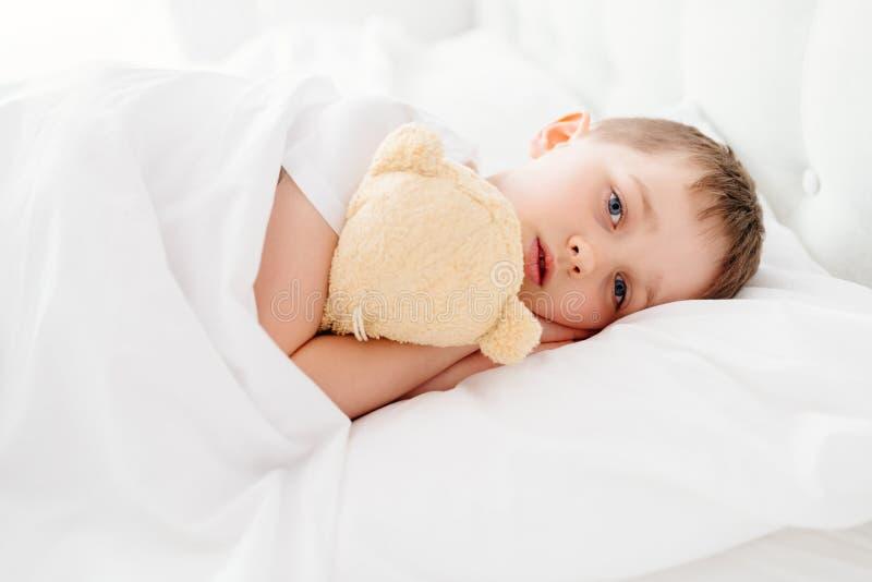 Niño del niño pequeño soñoliento en cama imagenes de archivo