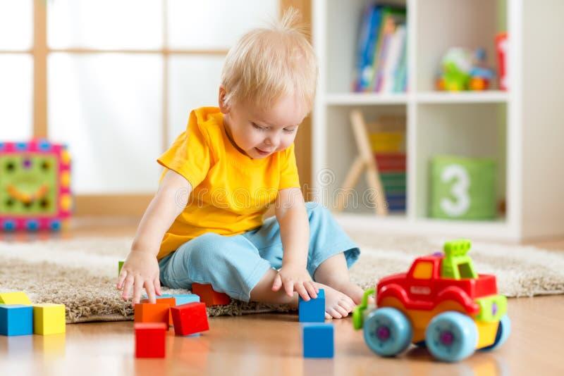 Niño del niño que juega bloques del juguete en su sitio o cuarto de niños fotografía de archivo