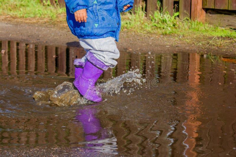 Niño del paseo del verano en las botas de goma en un charco foto de archivo