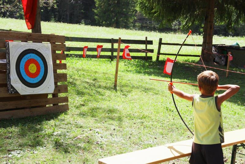 Niño del pelo rubio que juega a tiro al arco durante juegos del verano de los niños foto de archivo libre de regalías