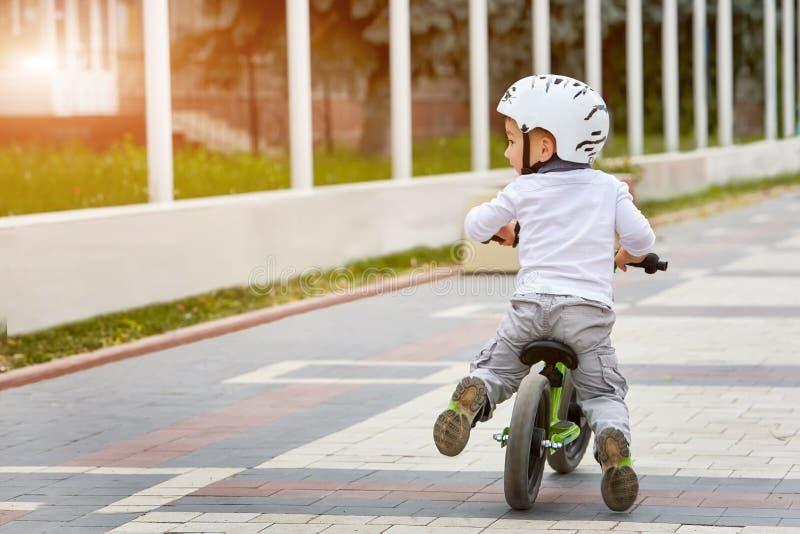 Niño del niño pequeño en paseo del casco una bici en parque de la ciudad Niño alegre al aire libre imagen de archivo