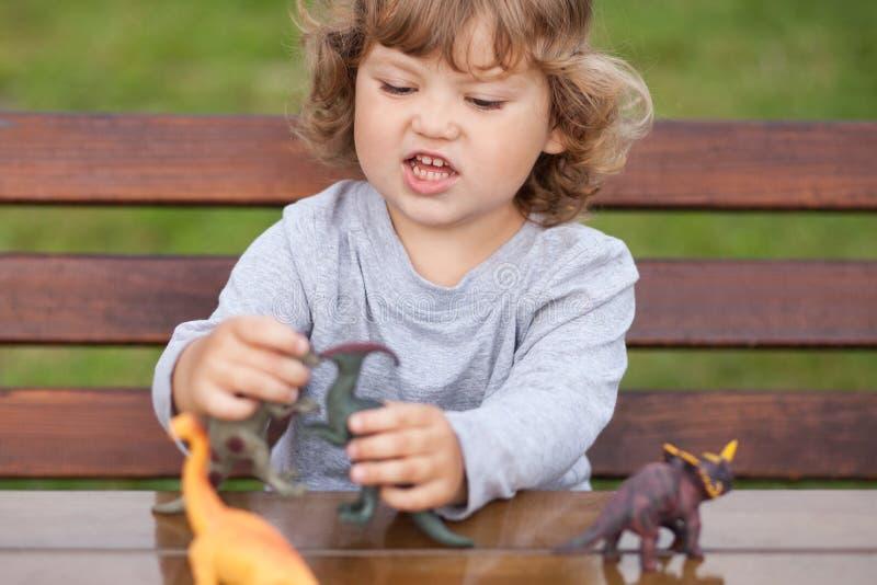 Niño del niño que juega con los dinosaurios de un juguete al aire libre imagen de archivo libre de regalías