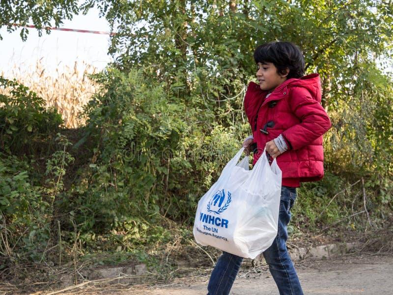 Niño del refugiado que lleva un malo de la ayuda humanitaria con el logotipo del ACNUR, la agencia de Naciones Unidas para los re foto de archivo libre de regalías