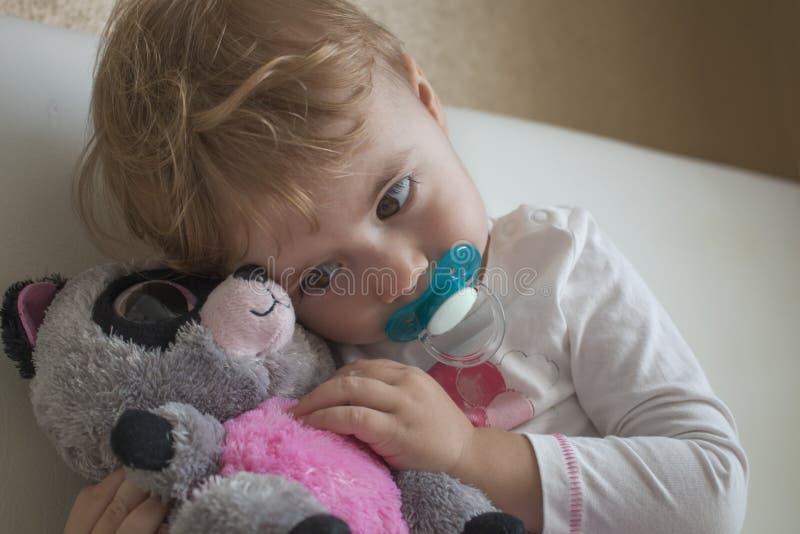 Niño del retrato de Clouse-up pequeño que se sienta en la cama en el cuarto que abraza un lémur relleno del juguete horizontal foto de archivo libre de regalías