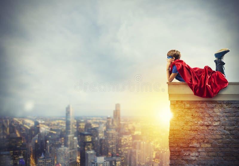 Niño del super héroe que sienta en una pared que sueños foto de archivo libre de regalías