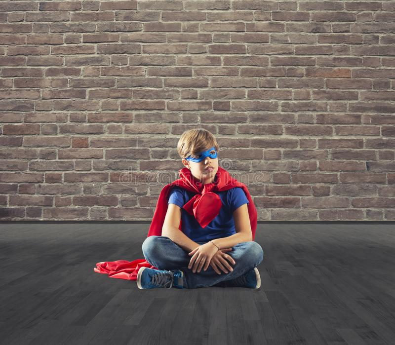 Niño del super héroe que sienta en una pared que sueños fotografía de archivo libre de regalías