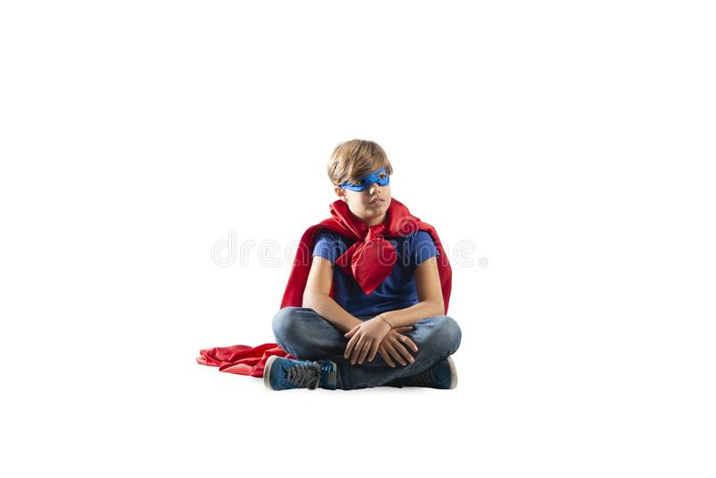 Niño del super héroe que sienta en una pared que sueños Aislado en el fondo blanco imagen de archivo libre de regalías