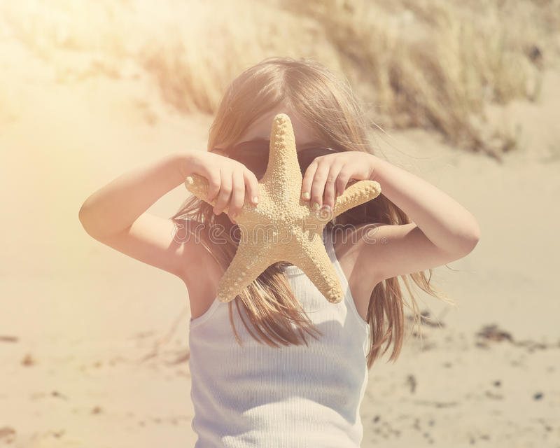 Niño del vintage en Sunny Beach con las estrellas de mar foto de archivo