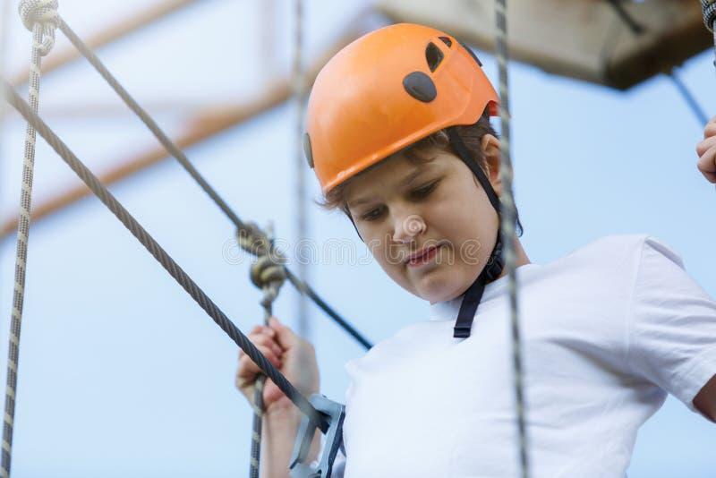 Niño deportivo activo en el casco que hace actividad en parque de la aventura con todo el equipo que sube Los niños activos suben fotos de archivo libres de regalías