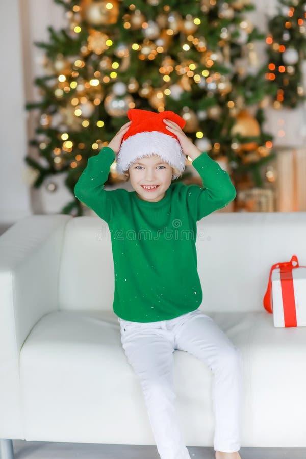Niño descalzo con pantalones blancos en la víspera de Año Nuevo está tirado en el sofá fotos de archivo libres de regalías