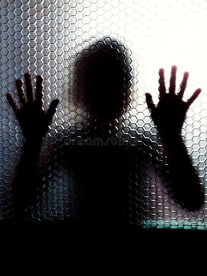 Niño detrás de la puerta de cristal que muestra las manos foto de archivo