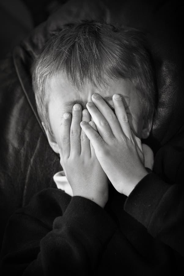 Niño detrás de las manos fotografía de archivo libre de regalías