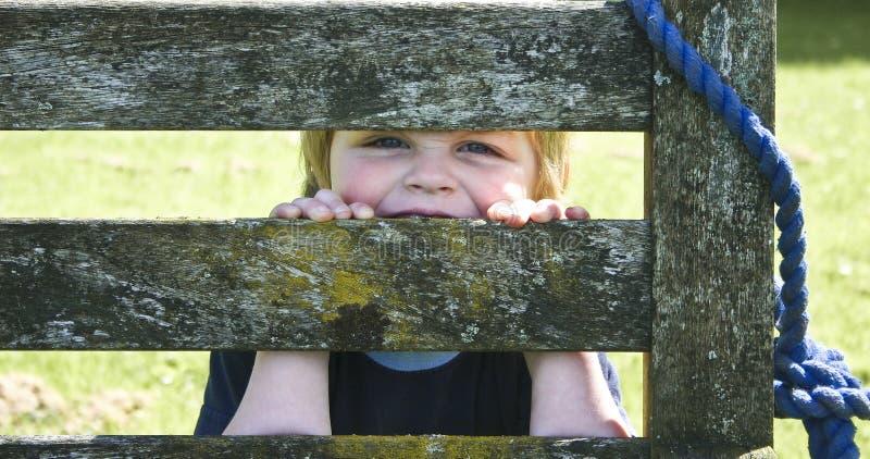 Niño detrás de un banco imagen de archivo