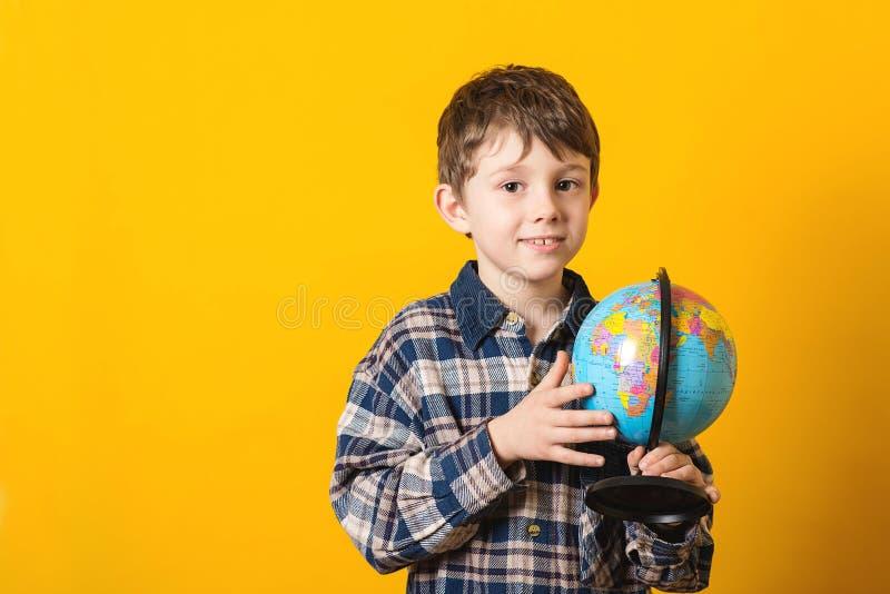 Niño divertido con el globo, aislado en amarillo De nuevo a concepto de la escuela Globo educativo Niño curioso que sostiene el m fotos de archivo libres de regalías