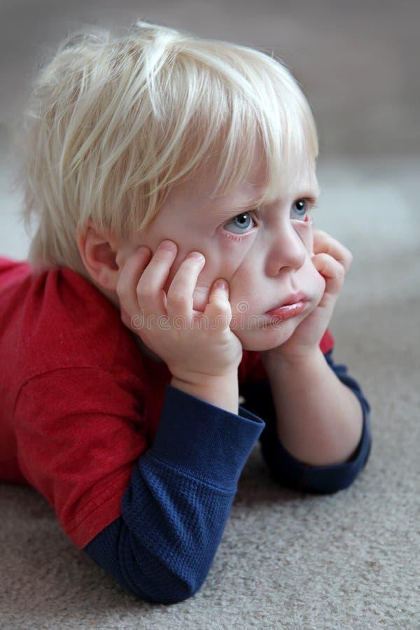 Niño divertido del niño que parece gruñón o el poner mala cara imagenes de archivo