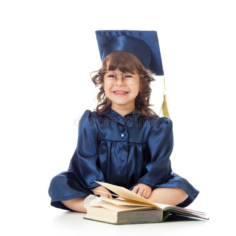 Niño divertido en ropa del académico con el libro fotografía de archivo