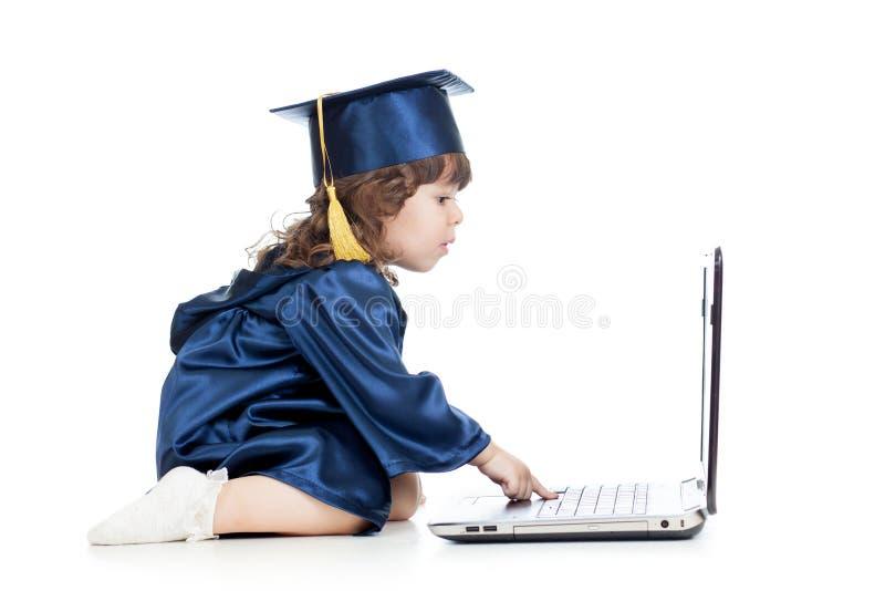 Niño divertido en ropa del académico usando el ordenador portátil fotografía de archivo