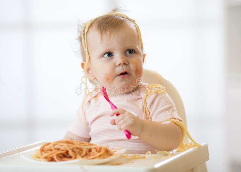 Niño divertido que come los tallarines El niño mugriento come los espaguetis con la bifurcación que se sienta en la tabla en casa imagen de archivo libre de regalías