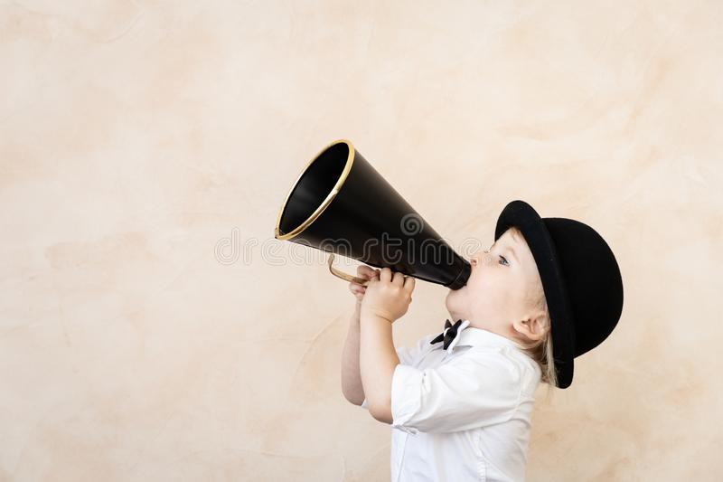 Niño divertido que juega con el megáfono retro negro imágenes de archivo libres de regalías