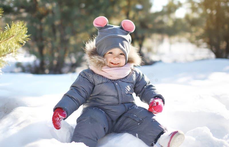 Niño divertido que juega en la nieve en día de invierno soleado imágenes de archivo libres de regalías