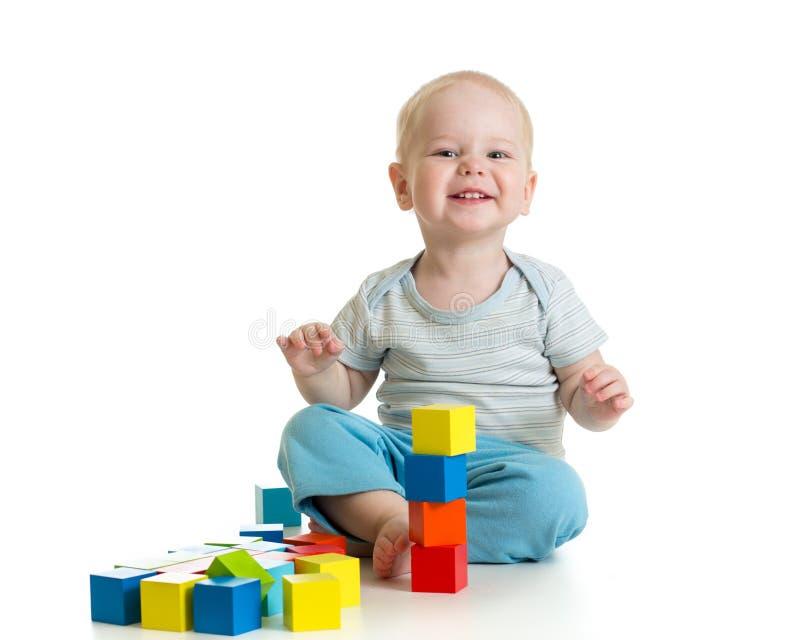 Niño divertido que juega los bloques de madera del juguete aislados en blanco imagen de archivo libre de regalías