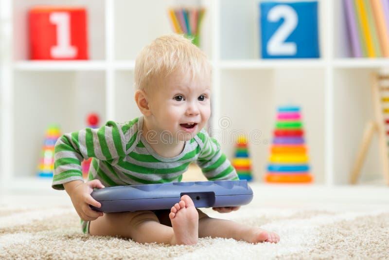 Niño divertido que se sienta en la alfombra con el juguete musical en cuarto de niños foto de archivo
