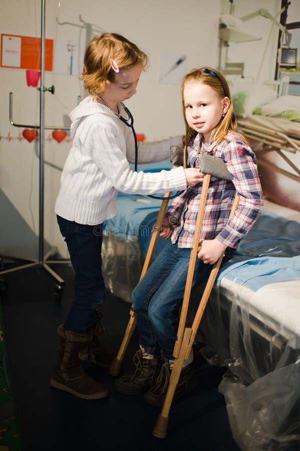 Niño dos que finge ser doctor y paciente - estetoscopio y embragues imagen de archivo libre de regalías