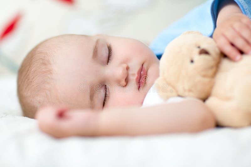 Niño durmiente del bebé en la cama, sosteniendo un oso de peluche foto de archivo