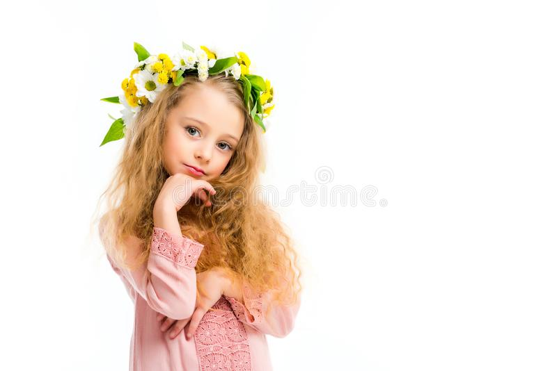 Niño elegante con la mano en banda de la guirnalda de la barbilla que lleva de las flores foto de archivo