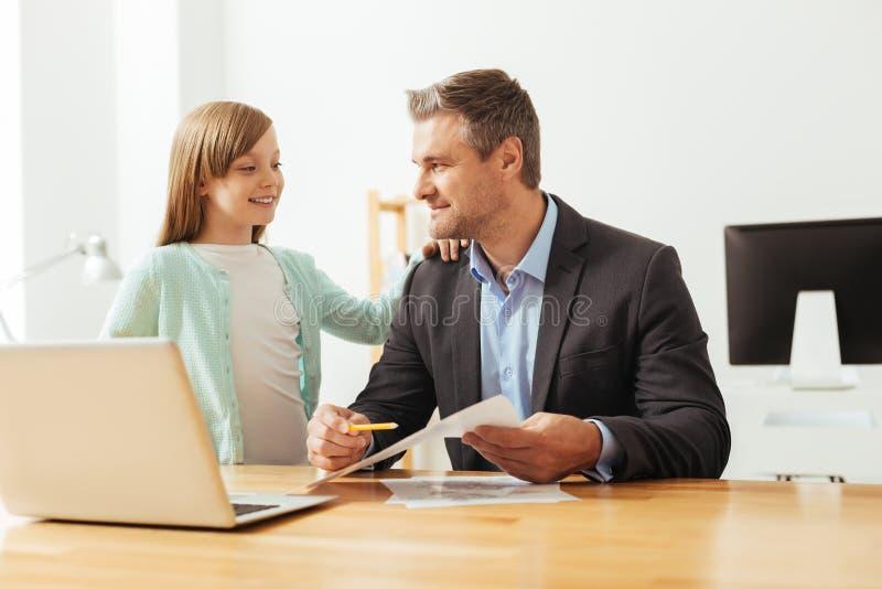 Niño elegante curioso que pregunta a papá acerca de su trabajo foto de archivo libre de regalías