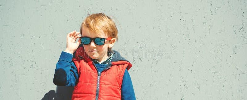 Niño elegante en gafas de sol de moda manera de los cabritos Pequeño blon lindo foto de archivo libre de regalías
