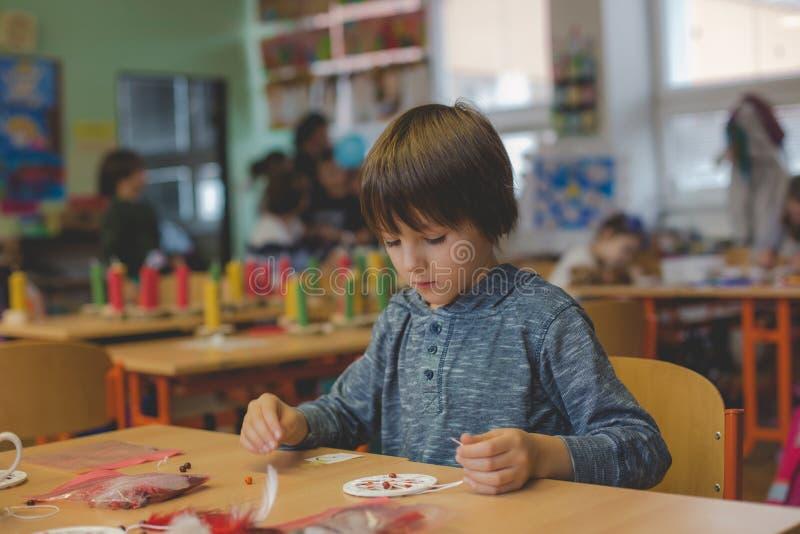 Niño elemental de la edad, creando arte y el producto del arte, colector ideal en la escuela en clase de arte foto de archivo