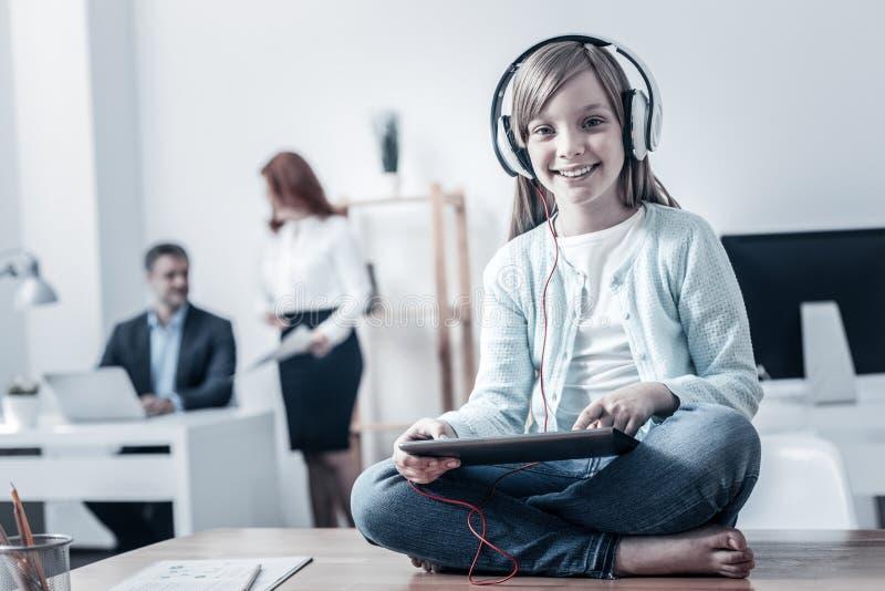 Niño emocionado que juega en la tableta en oficina fotos de archivo libres de regalías