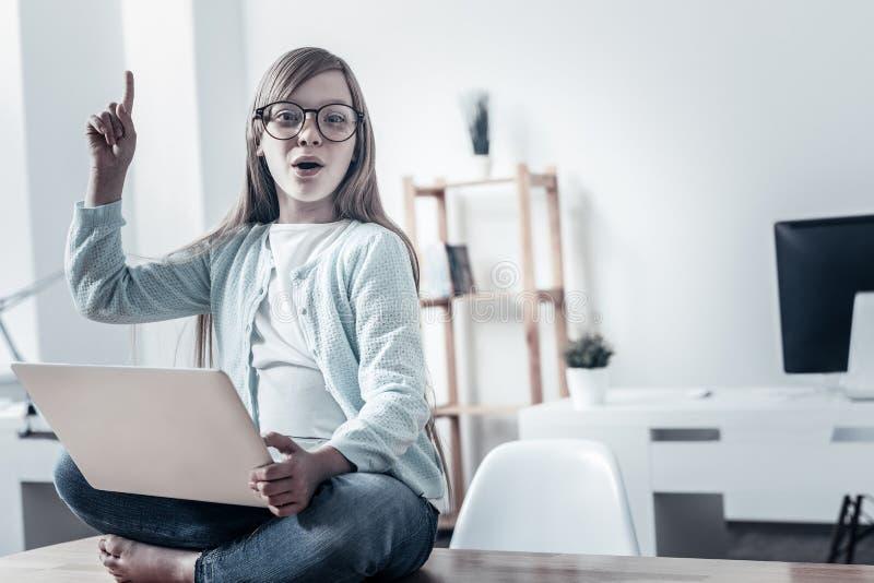 Niño emocionado que tiene nueva idea mientras que trabaja en el ordenador portátil imagenes de archivo