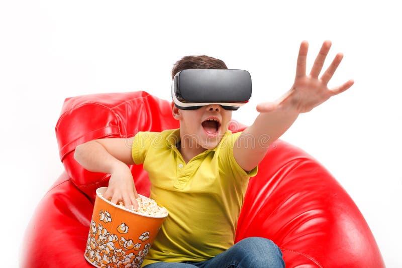 Niño en auriculares de VR con palomitas fotos de archivo