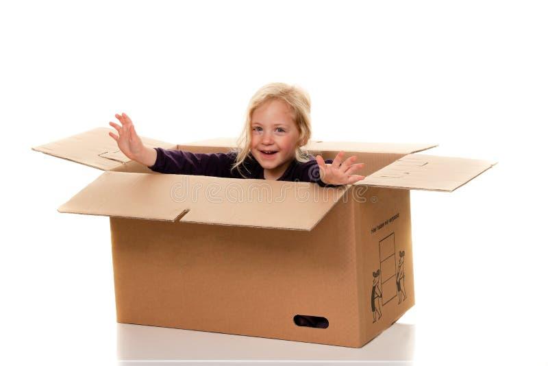 Niño en caja de cartón. Se está moviendo a los ejes fotos de archivo libres de regalías
