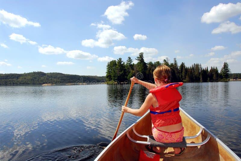 Niño en canoa imagen de archivo