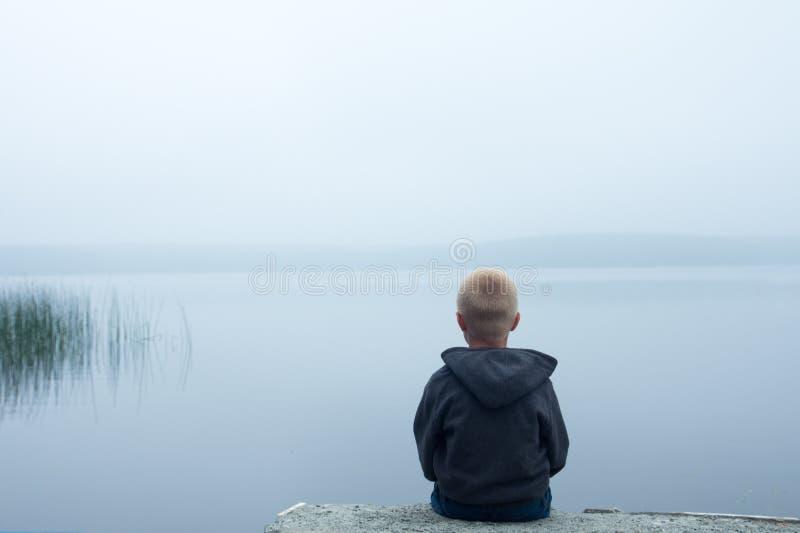 Niño en día de niebla fotografía de archivo
