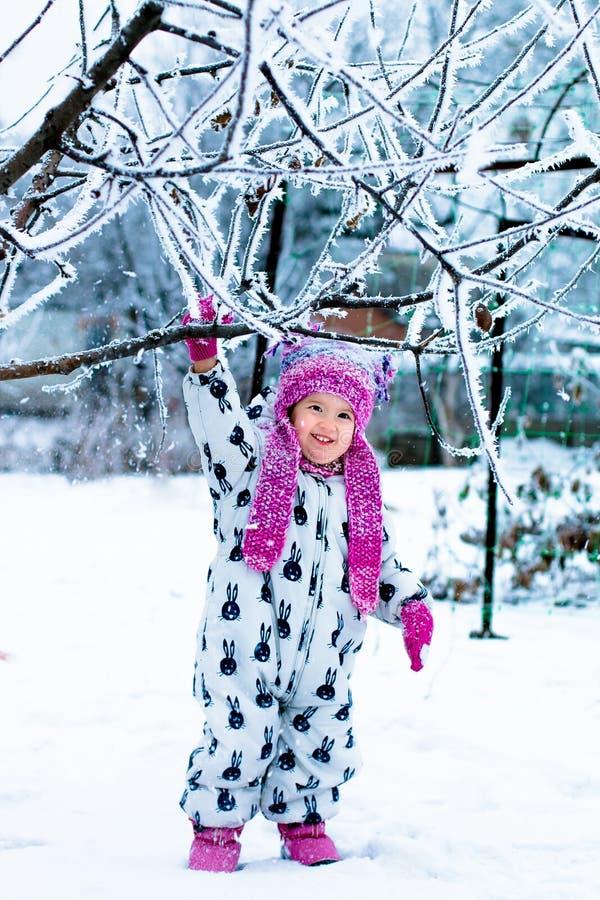 Niño en día nevoso El bebé en el snowsuite blanco y el sombrero rosado, guantes de las botas en el invierno de la nieve parquean  imagen de archivo