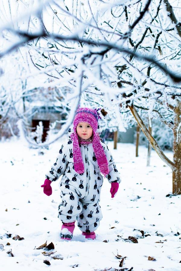Niño en día nevoso El bebé en el snowsuite blanco y el sombrero rosado, guantes de las botas en el invierno de la nieve parquean fotos de archivo