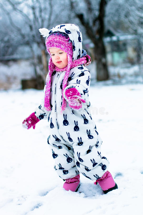 Niño en día nevoso El bebé en el snowsuite blanco y el sombrero rosado, guantes de las botas en el invierno de la nieve parquean foto de archivo libre de regalías
