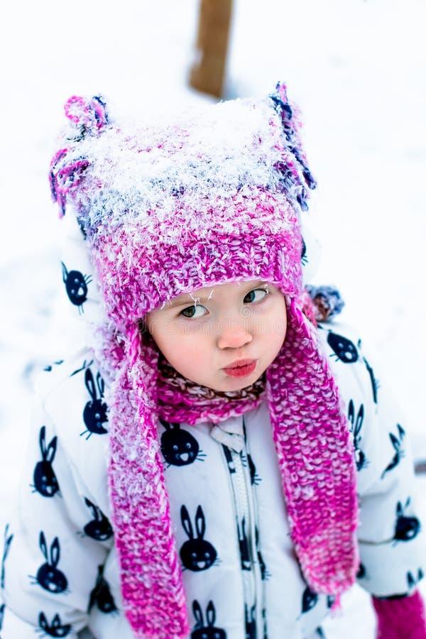 Niño en día nevoso El bebé en el snowsuite blanco y el sombrero rosado, guantes de las botas en el invierno de la nieve parquean foto de archivo