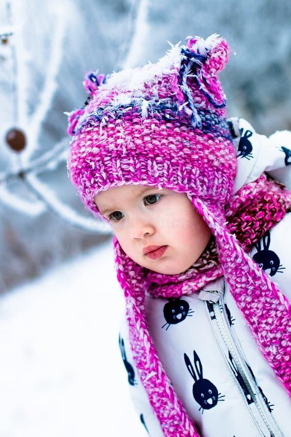Niño en día nevoso El bebé en el snowsuite blanco y el sombrero rosado, guantes de las botas en el invierno de la nieve parquean imagenes de archivo