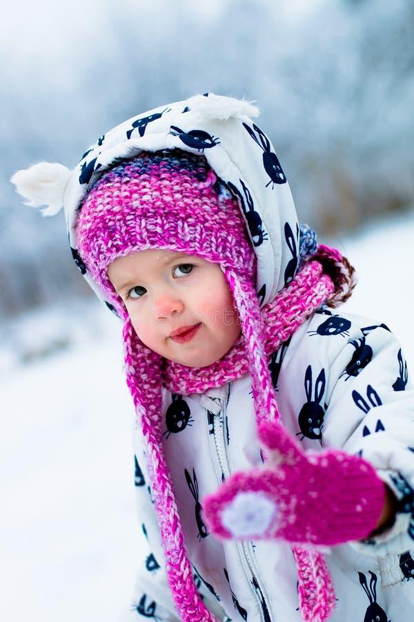 Niño en día nevoso El bebé en el snowsuite blanco y el sombrero rosado, guantes de las botas en el invierno de la nieve parquean imagen de archivo libre de regalías