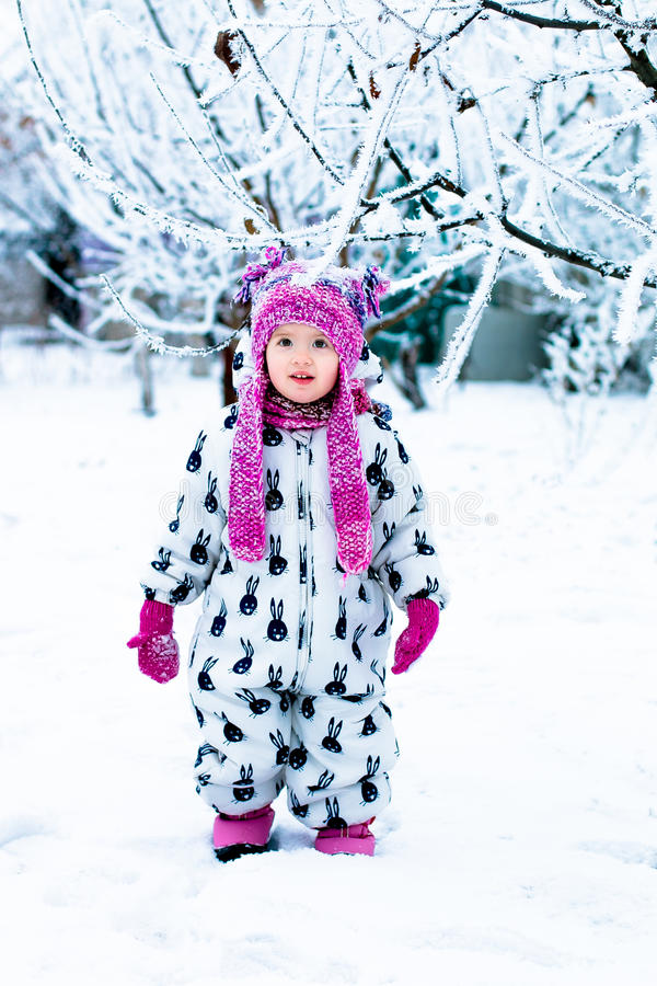 Niño en día nevoso El bebé en el snowsuite blanco y el sombrero rosado, guantes de las botas en el invierno de la nieve parquean fotografía de archivo libre de regalías