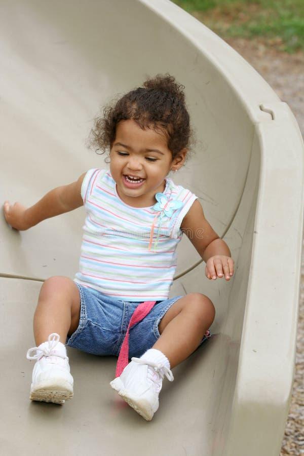 Niño en diapositiva del patio foto de archivo