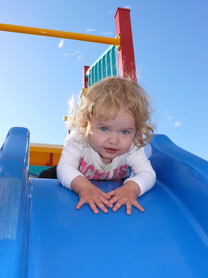 Niño en diapositiva deslizadiza foto de archivo