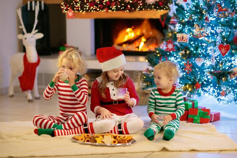 Niño en el árbol de navidad Niños en la chimenea en Navidad foto de archivo libre de regalías